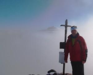 Der verschneite Ötschergipfel schaut aus der Nebeldecke heraus